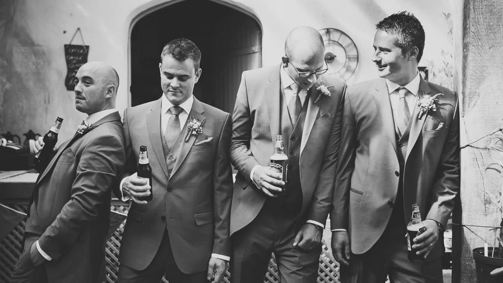 Black and white image of groom with his groomsmen having a beer