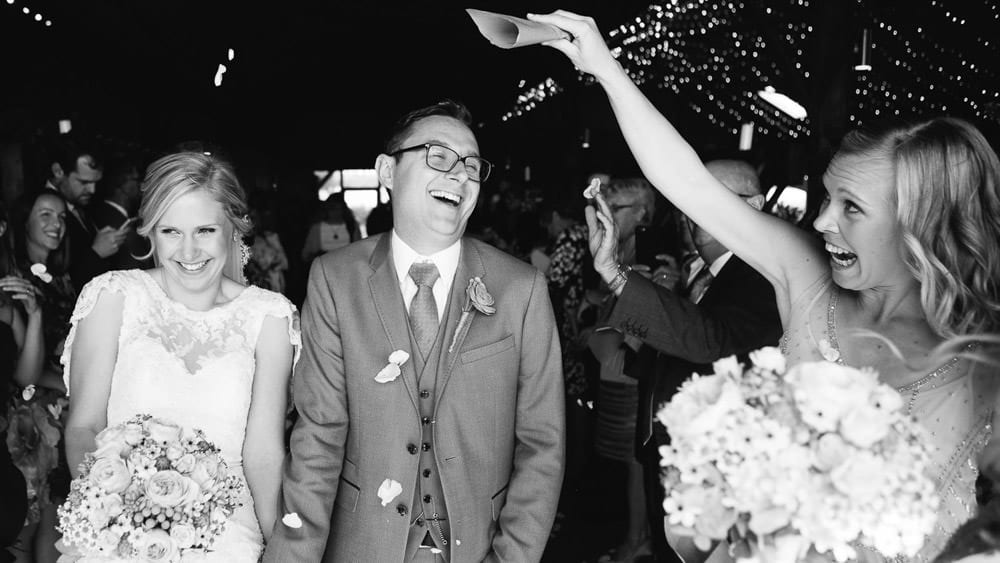 Black and white image of couple getting showered in confetti