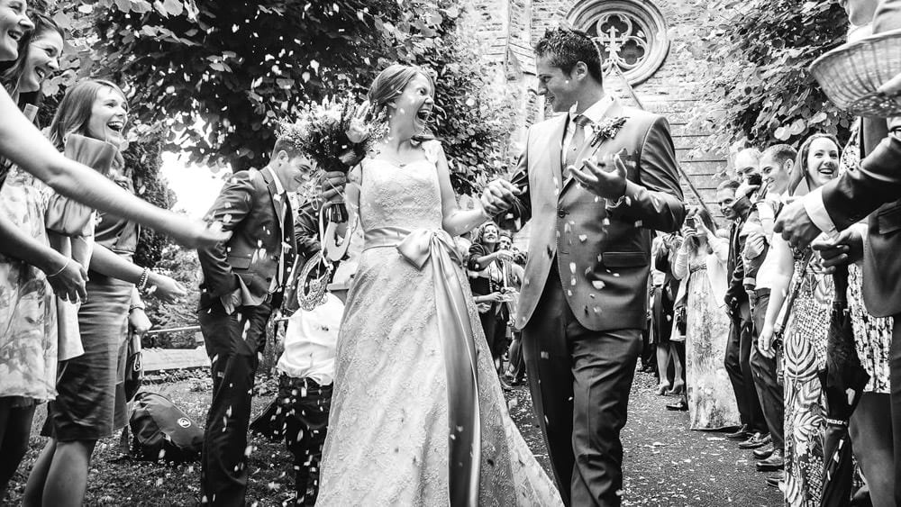 Black and white image of bride & groom walking through confetti