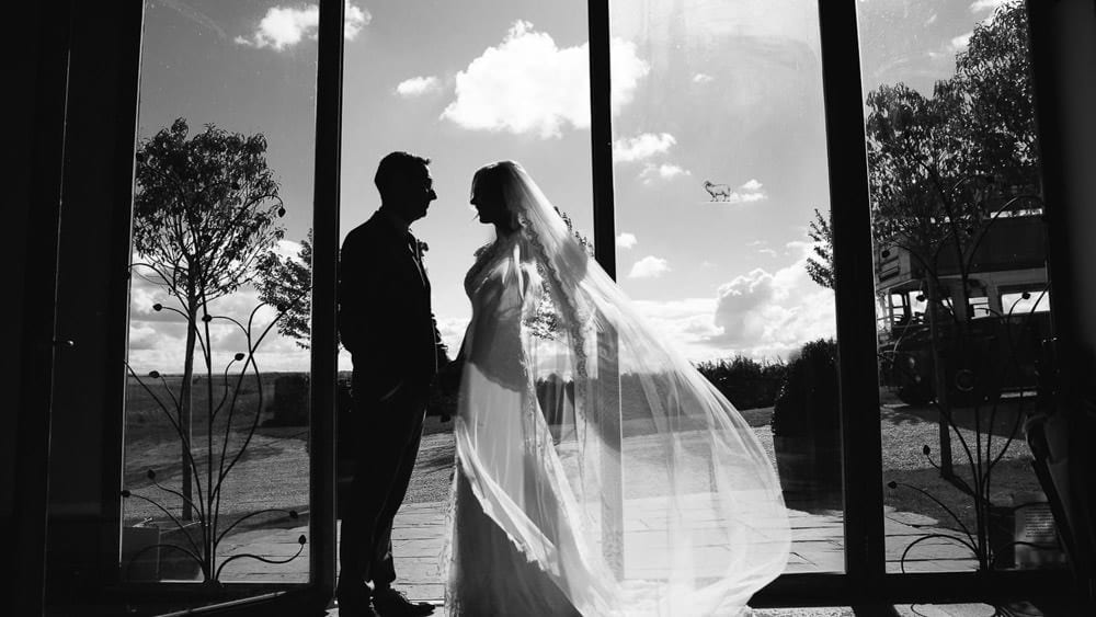 Black and white image of bride and groom by the doors at Stone Barn