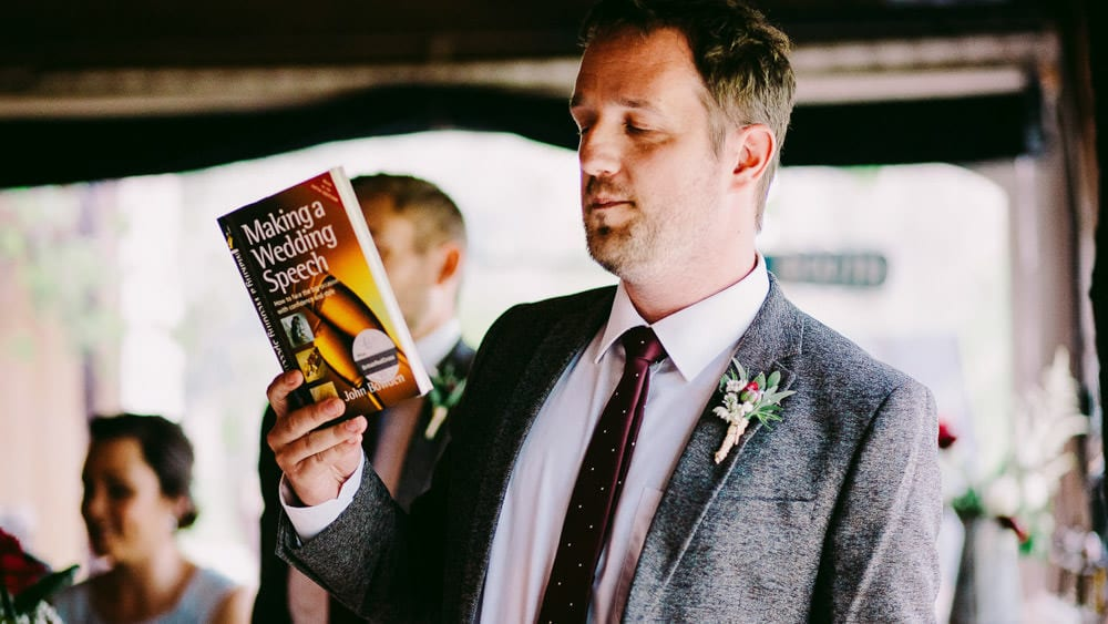 Best man holding a book on how to do his speech at Dewsall Court
