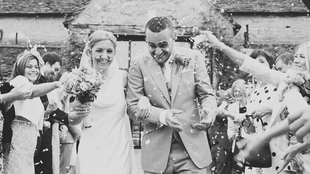 Bride and groom walking through confetti at Great Tythe Barn