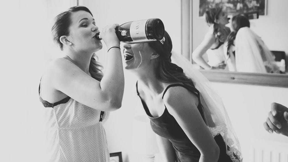 Bride and bridesmaid drinking champagne from the bottle during bridal preparation