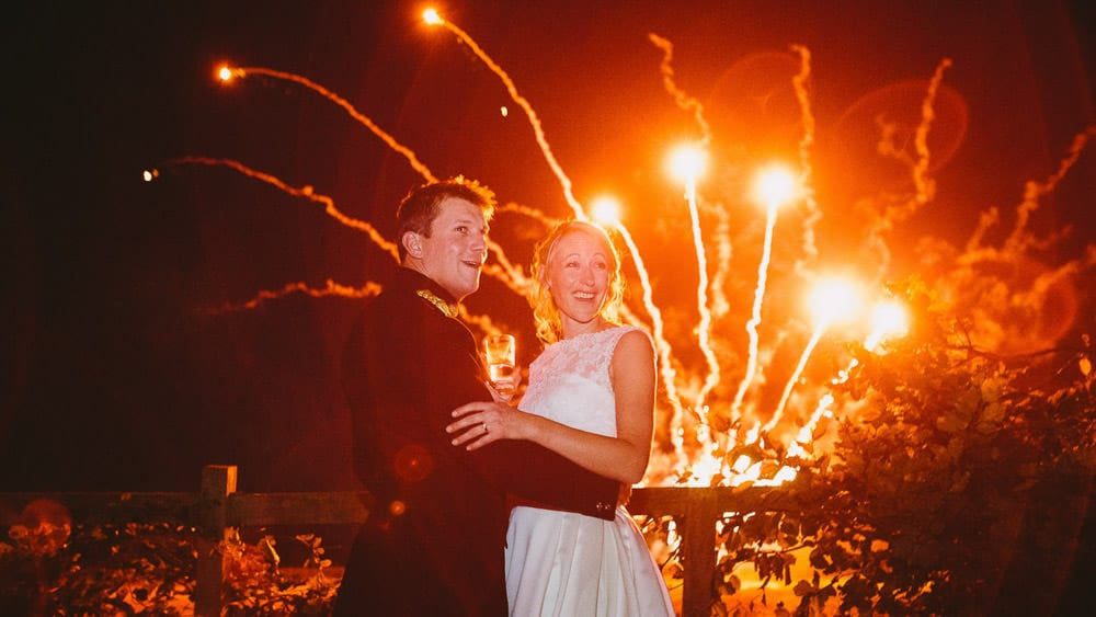 A bride and groom looking back at their guests while fireworks go off in the background
