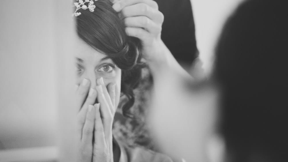 Bride looking at her headress in the mirror for Grittleton wedding