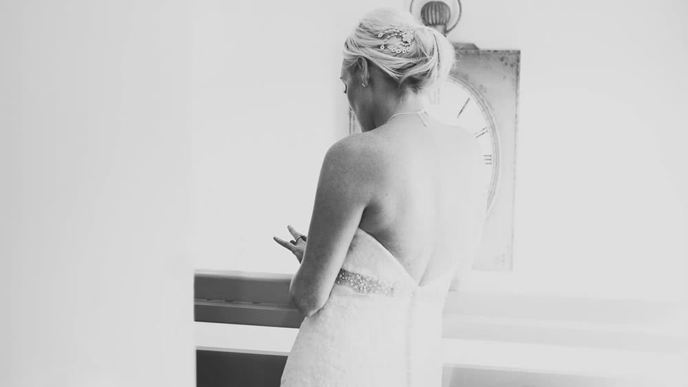 A bride examines her ring on the stairs at Sopley Mill
