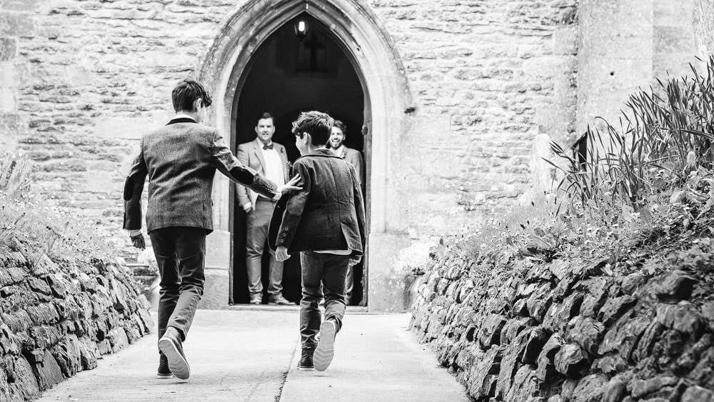 A page boy shoves his brother as they walk to the church
