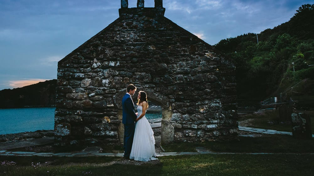 A newly married couple pose infront of a ruined church in Pembrokeshire