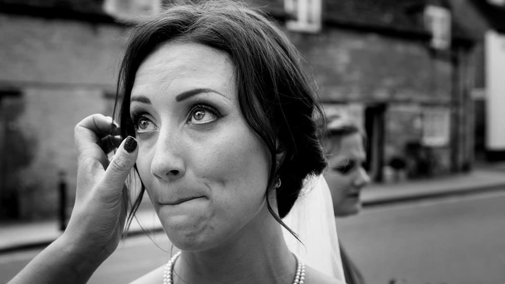 Black and white image of bride shedding a tear before her wedding