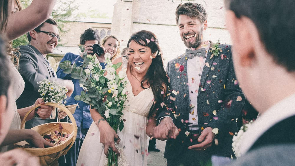 The bride and groom covered in confetti leave the church