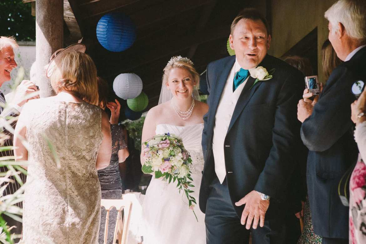 Dad leads his daughter, at quite a pace, through the guests to meet her groom