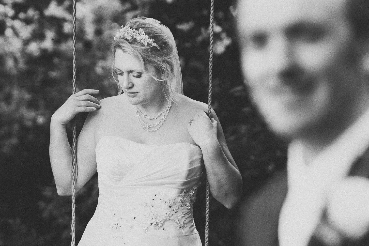 Bride stands on a swing while the groom looks on
