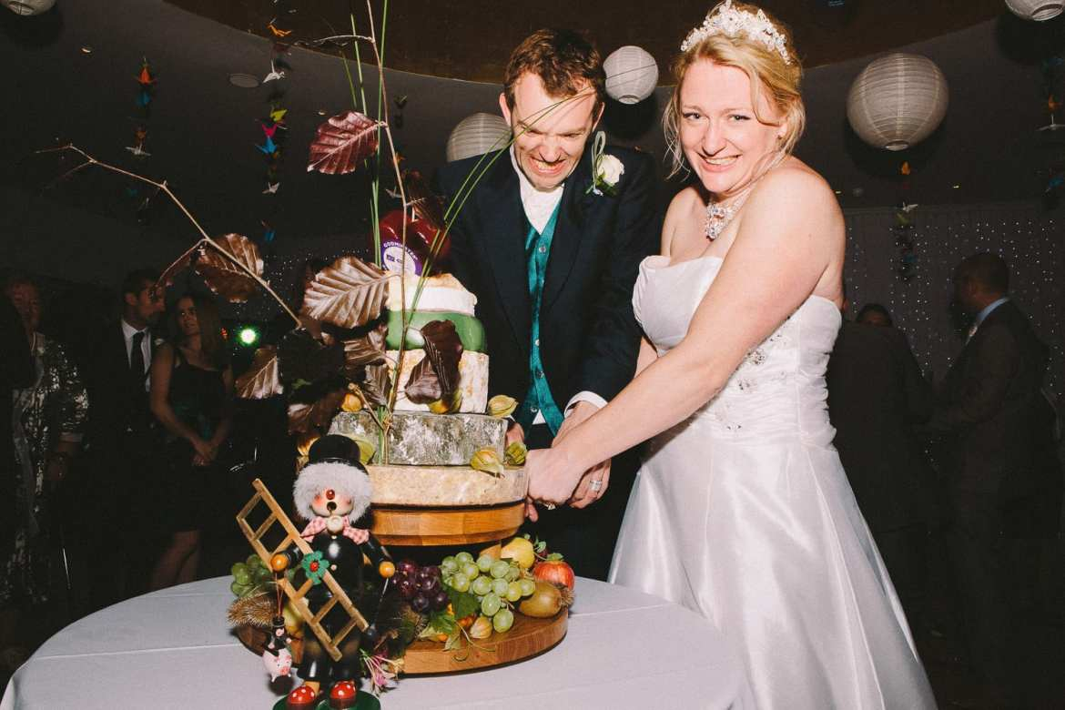 The couple struggle to cut their cheese tower wedding cake