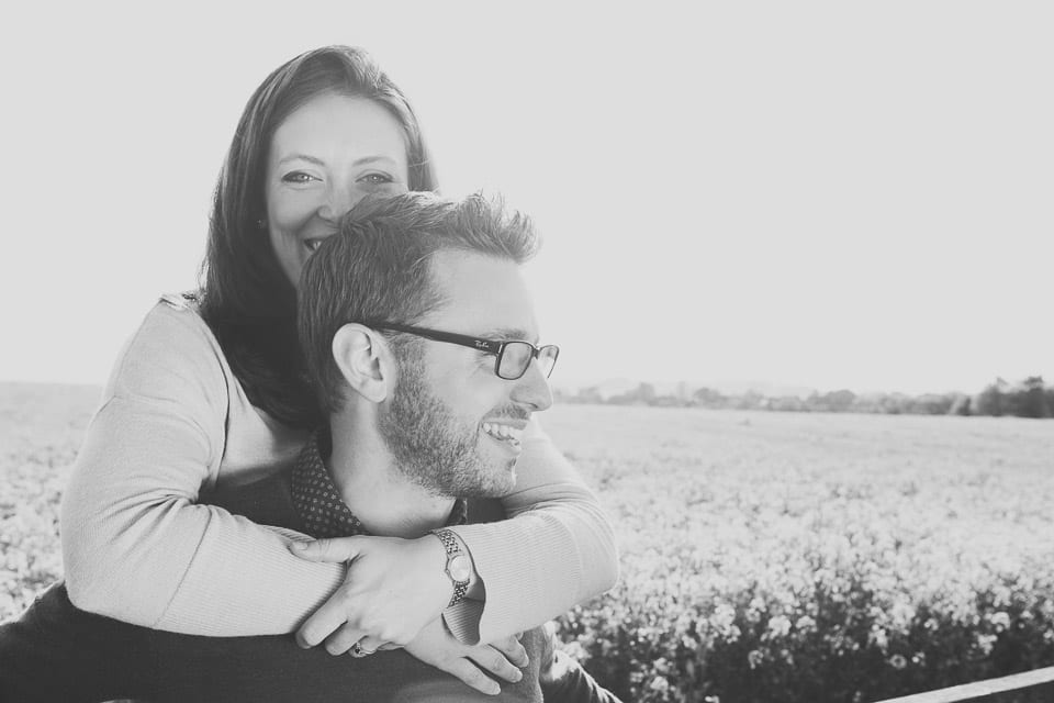 Black and white image of engaged couple sitting on a fence at Avebury