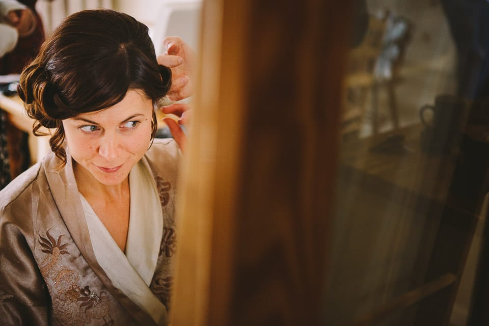 The bride checks her hair in the mirror