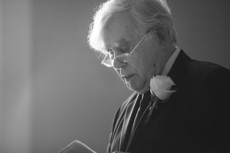 The bride's grandfather reads his notes during the wedding ceremony