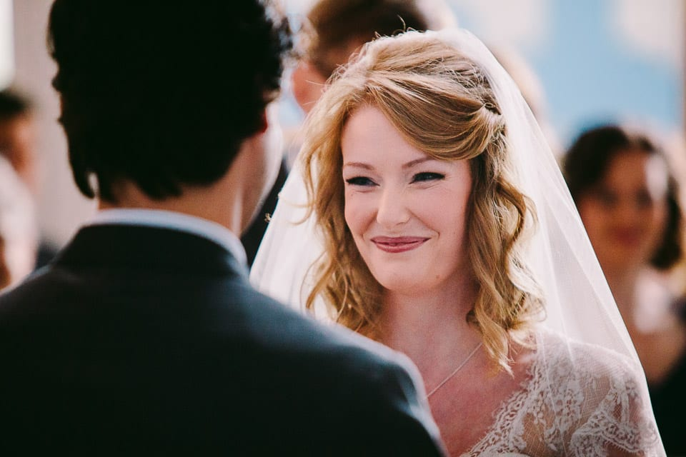 The smiling bride and groom face each other