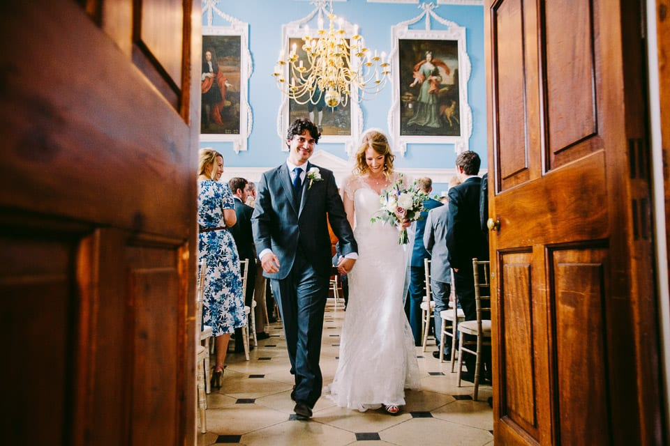 The bride and groom exiting the picture gallery after the ceremony at Kings Weston House