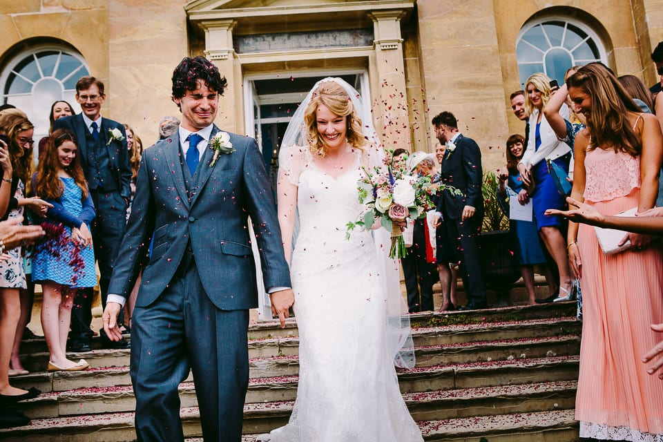 The groom gets a face full of confetti on the steps of Kings weston House