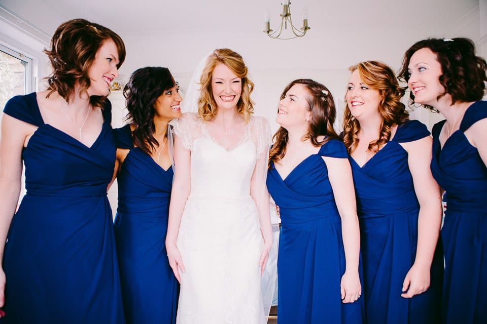The bride and bridesmaids lined up and laughing