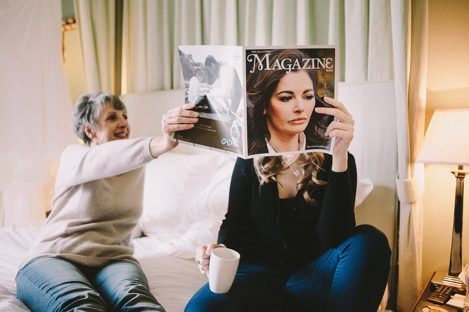 Bridesmaid reading a magazine on the bed with the Bride's mother