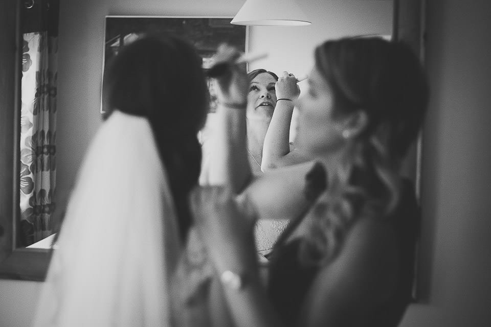 Bridesmaid helping bride with her make up at home