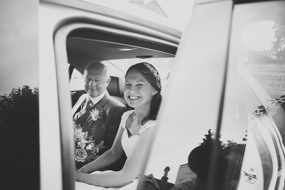 Black and white image of bride in the wedding car with her father