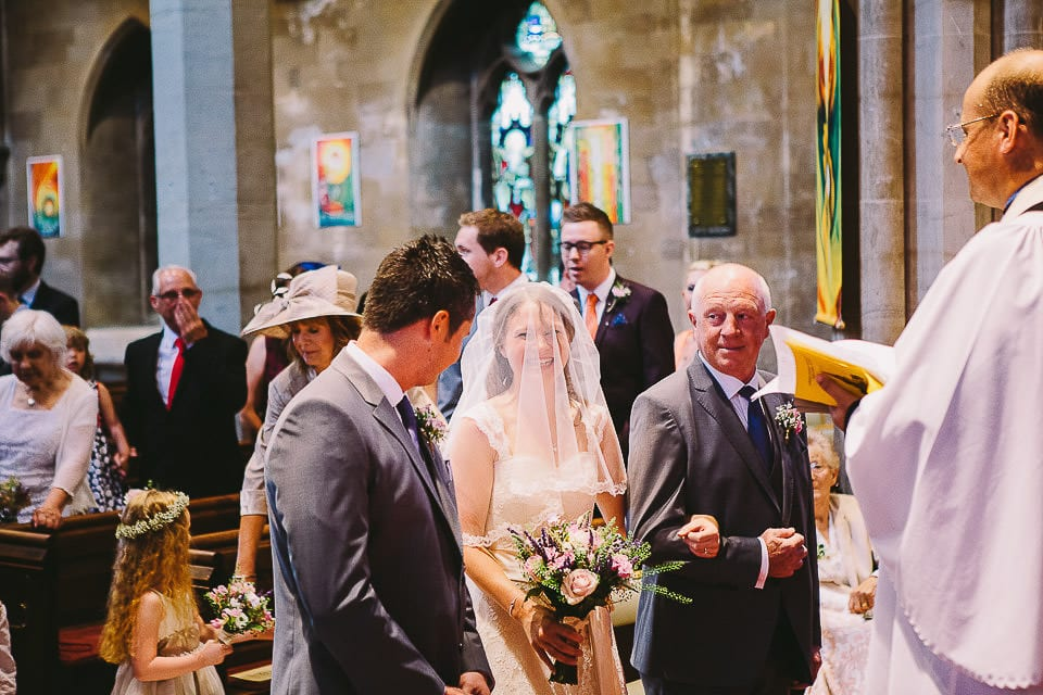 Groom looks at his bride as she arrives with her father at Christ Church