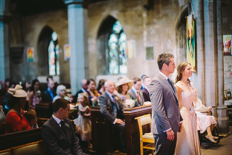 Bride and groom standing at the front of Christ Church during ceremony