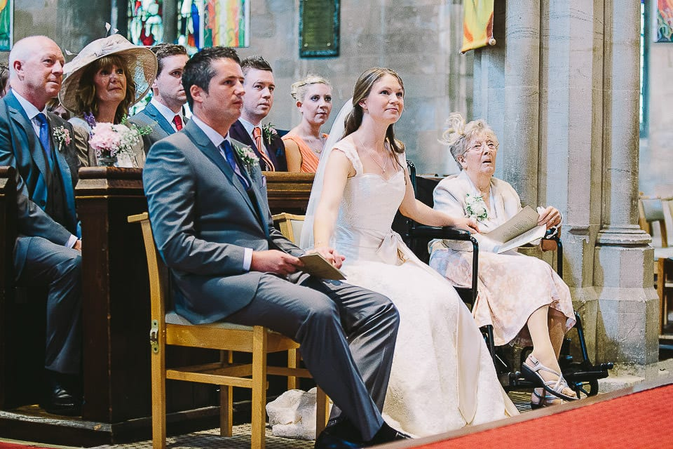Bride and groom seated in church during a reading