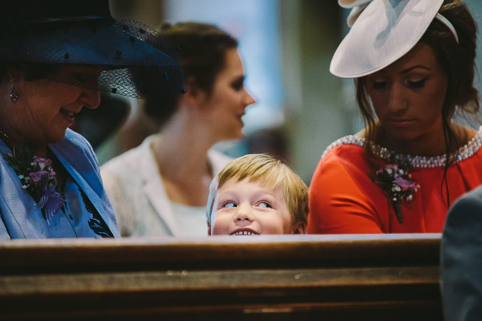 Young wedding guest peeking over a church pew