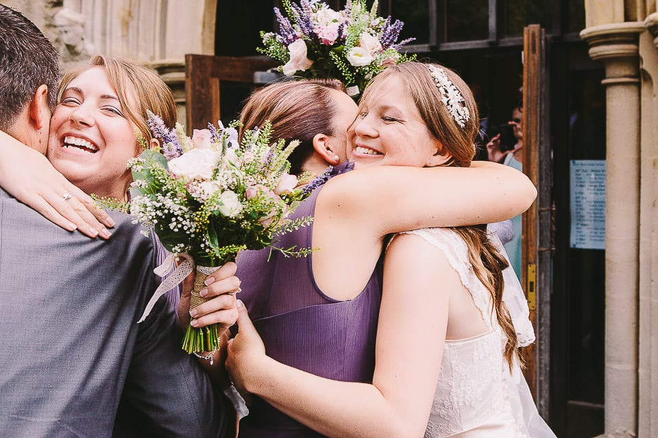 Bride hugging her bridesmaid outside the church