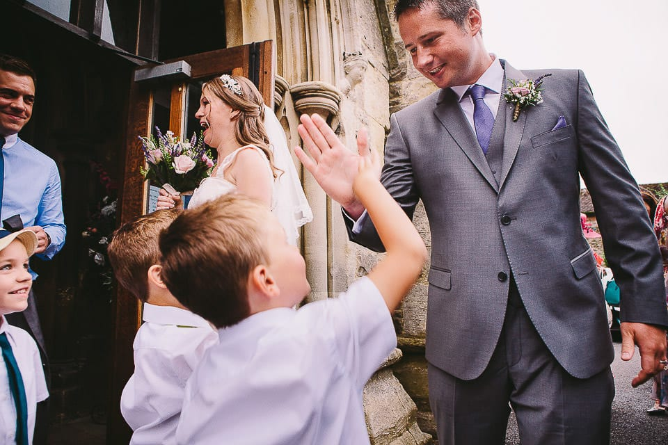 Groom giving a high five to a young wedding guest