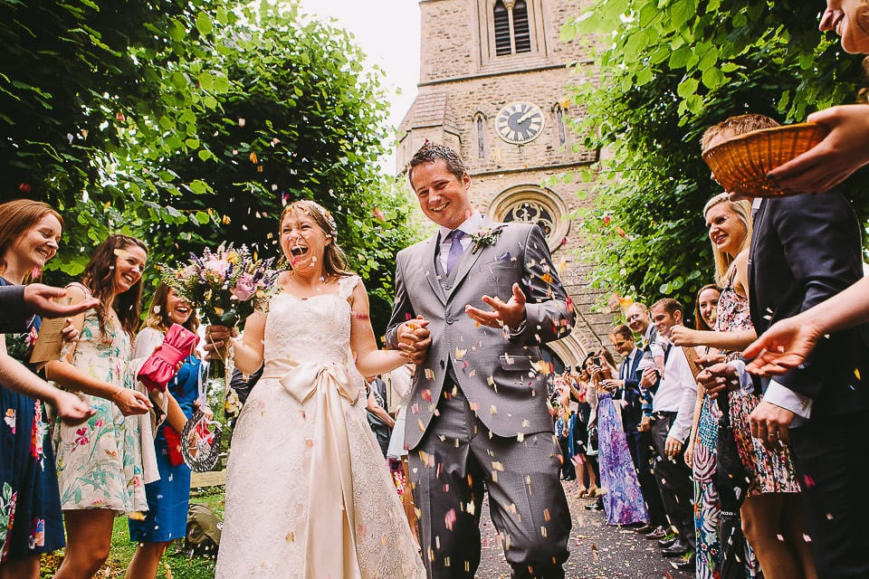 Bride and groom walking through confetti tunnel outside church