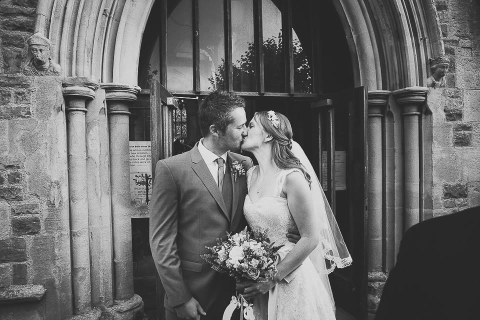 Bride and groom sharing a kiss in the church doorway