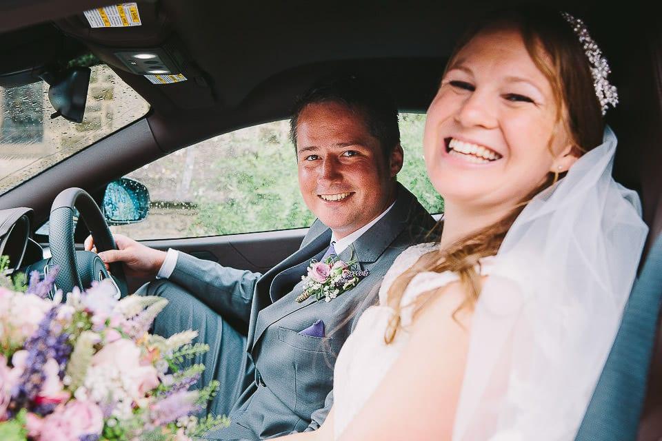 Bride and groom sitting in McLaren wedding car