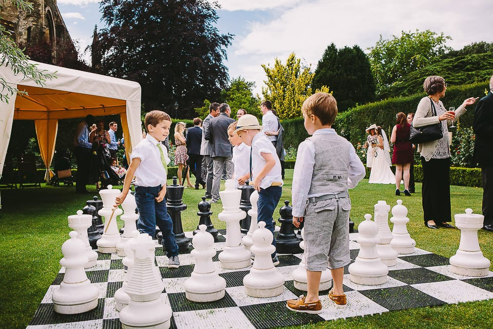 Young wedding guests playing giant chess at Abbey House Gardens
