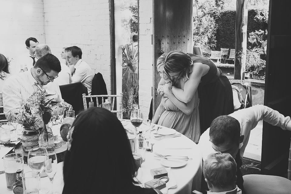 Bridesmaid hugging one of her friends at the table at Abbey House Gardens