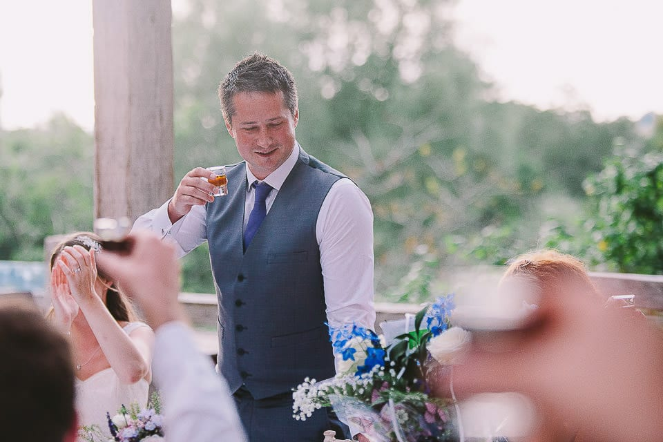 Groom drinking a shot during his speech at Abbey House Gardens