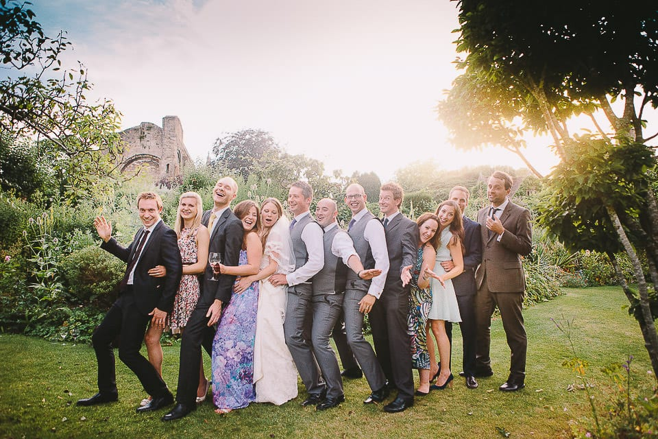 Bride and groom and their uni friends messing about at Abbey House Gardens