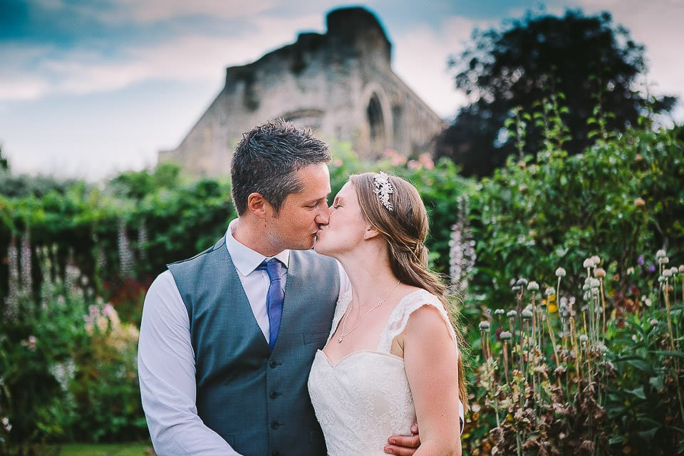 Portrait of bride and groom kissing in the gardens with Abbey in the background at Abbey House Gardens