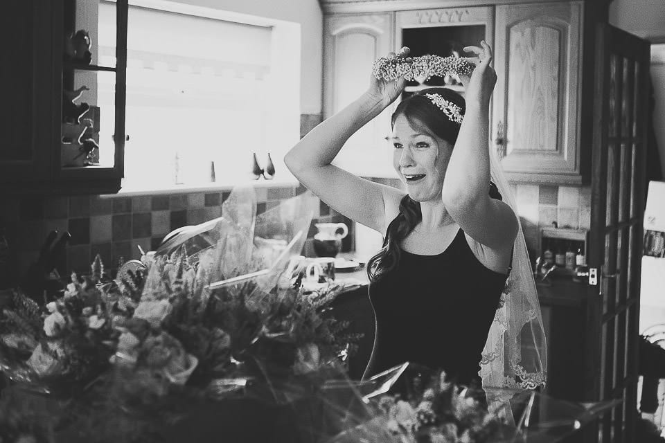 Bride in the kitchen trying flowers on her head