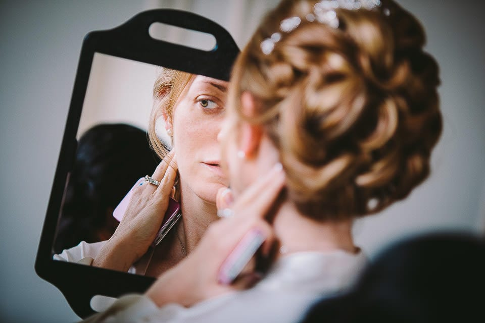 Bride holding a hand mirror to look at her finished hair at Bath Spa Hotel
