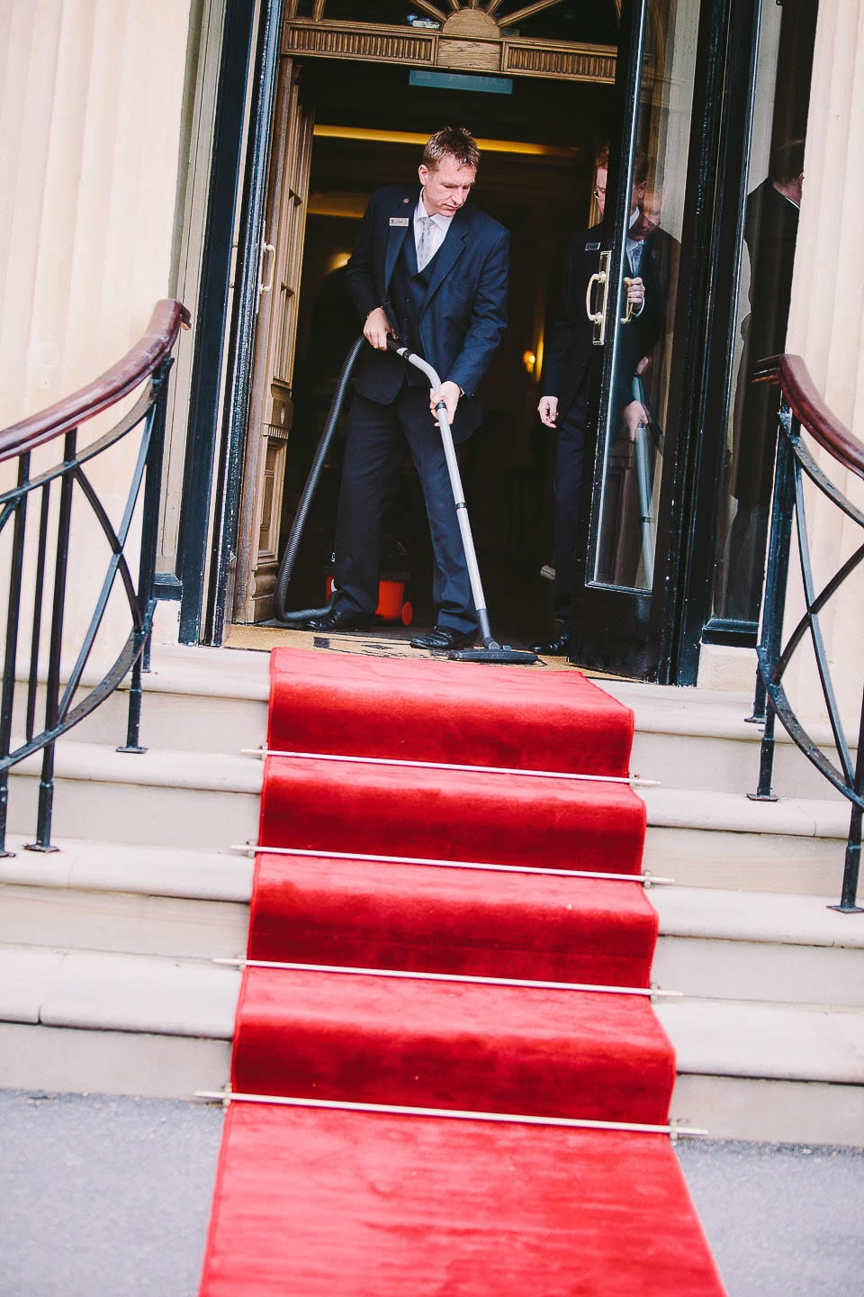 Staff vacuuming the red carpet on the steps at Bath Spa Hotel