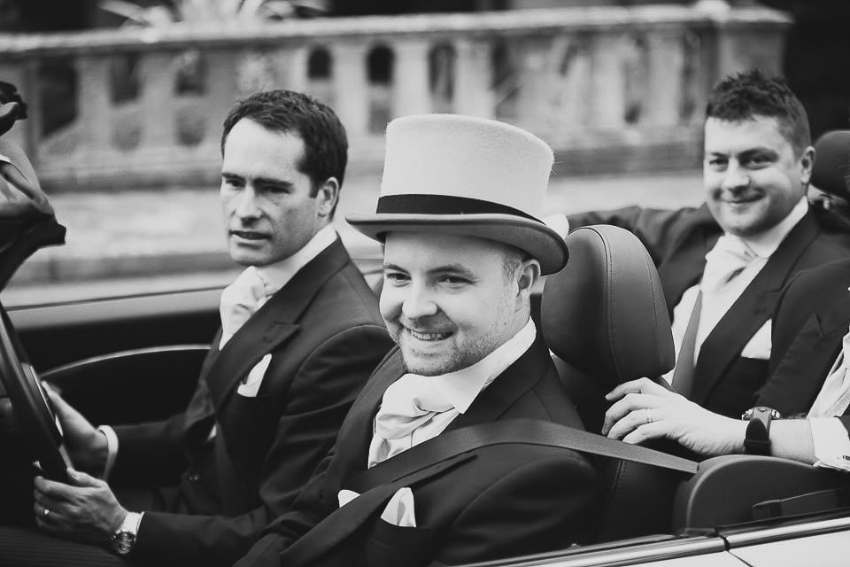 Black and white image of groom arriving in open top Mini at Bath Spa Hotel