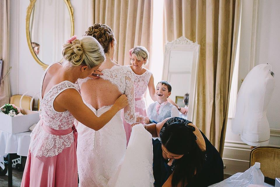 Bridesmaids helping bride get into her wedding dress at Bath Spa Hotel