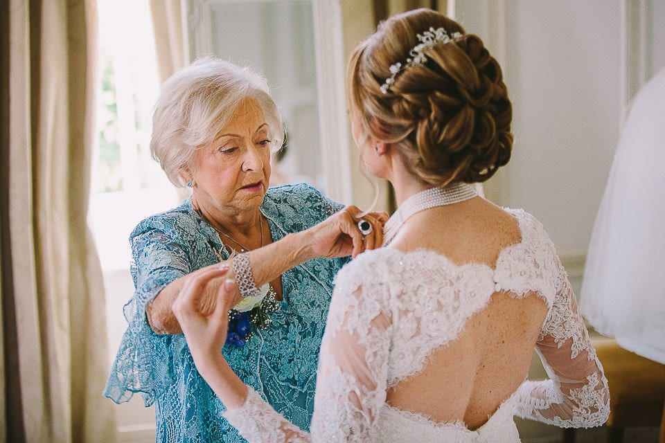 Mother of the bride helping her into her dress at Bath Spa Hotel