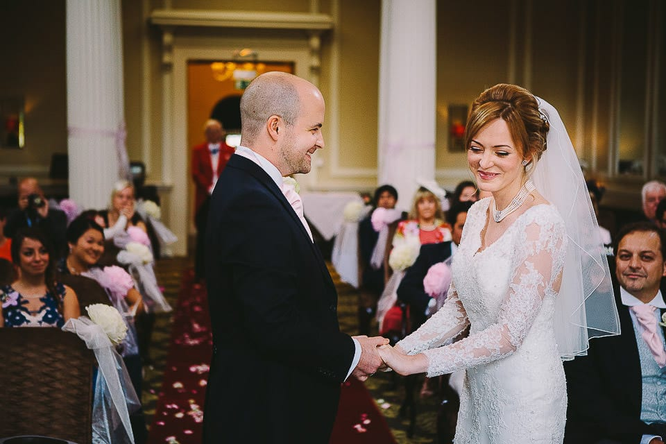 Bride and groom holding hands during ceremony at Bath Spa Hotel