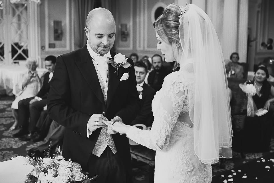 Black and white image of bride and groom exchanging rings at Bath Spa Hotel