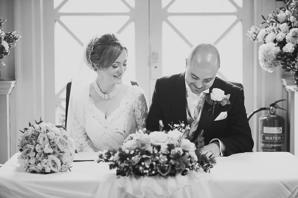 Black and white image of groom signing the register at Bath Spa Hotel
